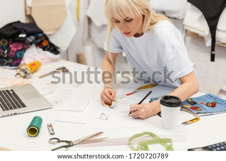 Young beautiful fashion designer seamstress draws a sketch at the workplace with a laptop, centimeter, coffee, thread, scissors, cloth and other tools. Concept production of a fashionable new