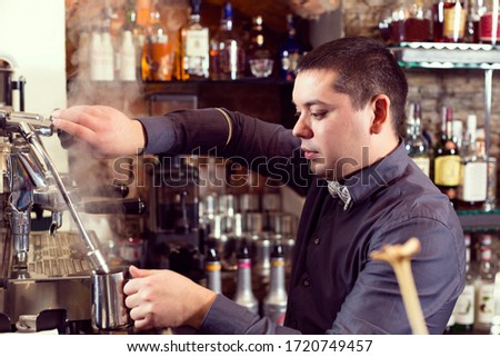 A young guy working as a bartender behind a bar is preparing drinks for customers. #1720749457