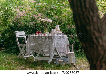 Pink peonies in a glass vase and books in lilac covers, sweets, marshmallows and ripe strawberries in a bowl on a white table in the backyard garden.