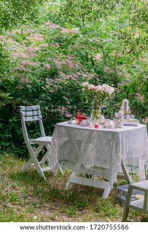 Pink peonies in a glass vase and books in lilac covers, sweets, marshmallows and ripe strawberries in a bowl on a white table in the backyard garden.Photo of a beautiful decor