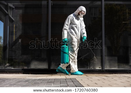 Full length of man in sterile uniform and mask sterilizing surface outdoors from corona virus, fungus and disease. Royalty-Free Stock Photo #1720760380