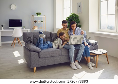 Happy family watching together video online in a laptop while sitting comfortably at home. #1720778893