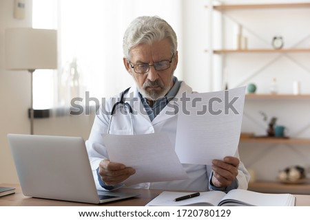 Serious professional senior elderly doctor doing paperwork checking medical documents at workplace. Concentrated old physician reading medic form analyzing patient diagnosis or report in hospital. Royalty-Free Stock Photo #1720780129