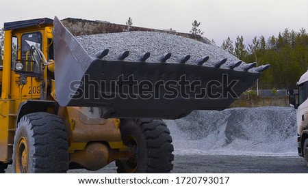 Tractor moves rubble to truck. Stock footage. Excavator-loader rakes rubble from pile at construction site and loads dump truck. Clearing site or mining rubble with heavy transport