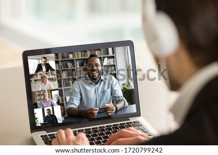 Back view of male employee in headphones have online webcam conference on computer with diverse colleagues, businessman talk speak on video call on laptop from home with multiracial coworkers #1720799242