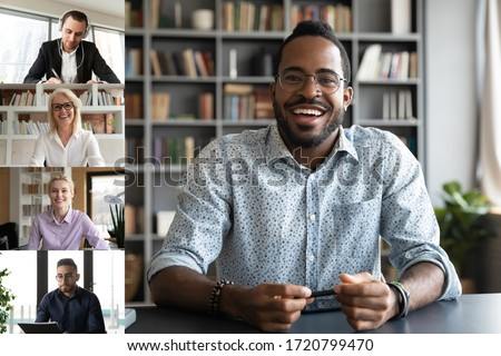 Smiling african American man worker talk brainstorm on video call with diverse colleagues, screen view of multiracial coworkers have webcam team work conference, engaged in web online briefing #1720799470
