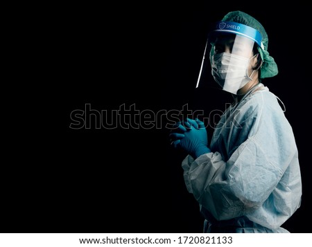 smart female Doctor wearing face shield and PPE suit and feeling motivate fighting Coronavirus outbreak or Covid-19, Concept of Covid-19 quarantine with black background #1720821133
