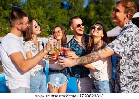 Group of friends having fun at poolside summer party clinking glasses with summer cocktails on sunny day near swimming pool. People toast drinking fresh juice at luxury villa on tropical vacation. #1720823818