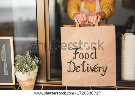 Young woman preparing food delivery inside ghost kitchen during quarantine isolation time - Take away meal for online order - Sustainable and healthy food concept - Focus on hands Royalty-Free Stock Photo #1720830919