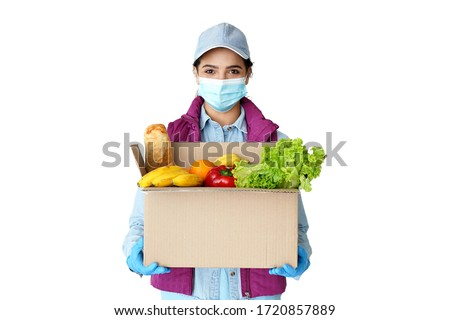 Young hispanic indian woman courier worker wears medical face mask, gloves looking at camera holding grocery food delivery box in hands concept stand isolated on white studio background. Portrait #1720857889