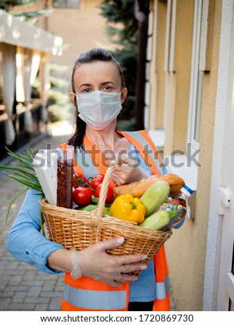 Portrait of a volunteer girl in a protective mask and medical gloves near the house of a man who is on self-isolation #1720869730