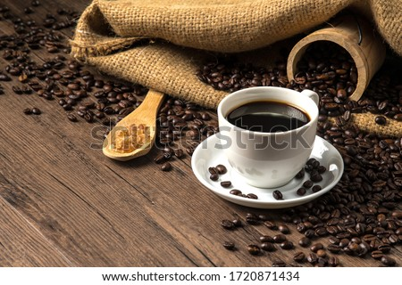 Hot coffee in a white coffee cup and many coffee beans placed around and sugar on a wooden table in a warm, light atmosphere, on dark background, with copy space. #1720871434