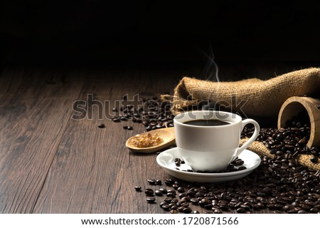 Hot coffee in a white coffee cup and many coffee beans placed around and sugar on a wooden table in a warm, light atmosphere, on dark background, with copy space. #1720871566