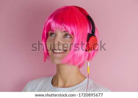 beautiful happy young woman with pink hair using red headphones and listening music on a pink background