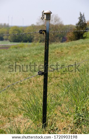 metallic post of a barbed wire fence #1720903198