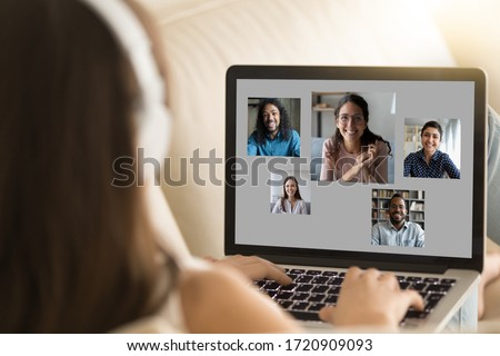 Back view of young female sit rest on sofa ta home talk chat online on video call on laptop with diverse friends, millennial girl have webcam conference on computer with multiracial pals or colleagues Royalty-Free Stock Photo #1720909093