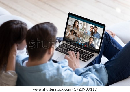 Back view of young couple relax on couch speak talk on video call with multiracial friends, man and woman spouses rest on sofa at home engaged in webcam conference conversation with relatives #1720909117