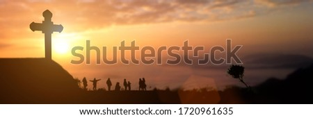 Silhouette of group people looking for the christian cross at sunset background. Idea for worship or praise god. panorama picture