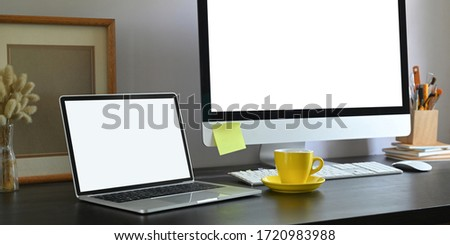 Workspace laptop with white blank screen putting on black working desk surrounded by wild grass in glass vase, empty picture frame, computer monitor with white screen, coffee cup and keyboard.