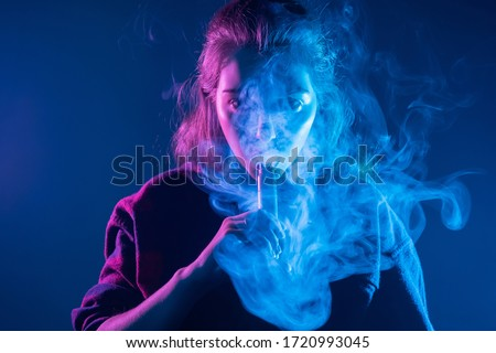 Smoking an electronic cigarette. The girl's face is covered with smoke from vape. Portrait of a female smoker in a cloud of smoke. A woman smokes a VAPE on a dark background. #1720993045