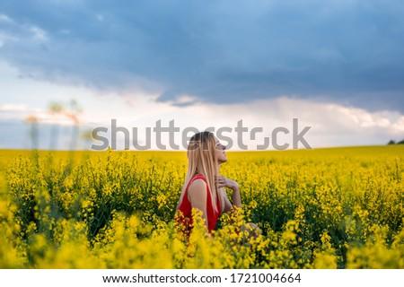 Beautiful blonde model in rapeseed field before storm #1721004664