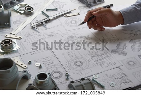 Engineer technician designing drawings mechanicalparts engineering Engine manufacturing factory Industry Industrial work project blueprints measuring bearings caliper tools Royalty-Free Stock Photo #1721005849