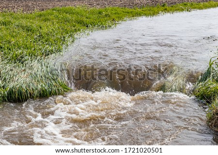 Water flowing in farm field waterway after heavy rain and storms caused flooding. Concept of soil erosion, water runoff control and management #1721020501