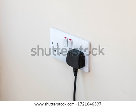Uk plug socket with a black plug plugged in wasting electricity  Royalty-Free Stock Photo #1721046397