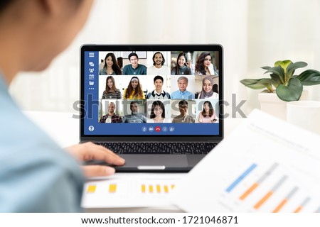 Back view of young asian business woman work remotely at home video conference remote call to corporate group. Meeting online,videocall, group discuss online concept with screen of teamwork on laptop. #1721046871
