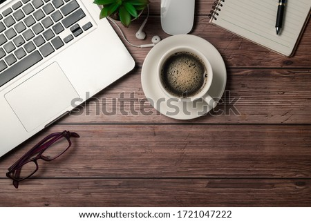 Old wood desk table with black coffee  and laptop computer, notebook and eye glasses. Top view with copy space, flat lay. #1721047222