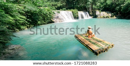 Woman in bikini and hat sitting on bamboo raft and enjoying view on waterfall. Travel and vacation concept. Banner and panoramic edition. #1721088283