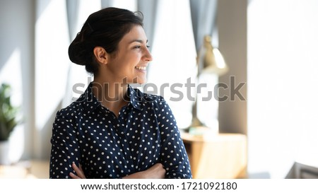 Head shot side view happy young indian girl standing with folded arms at home, looking at window. Successful smiling millennial hindu businesswoman dreaming visualizing future, planning holiday.