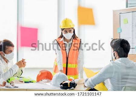 Group of creative building architect construction engineer project meeting and brainstorm together. Industry, Engineer, construction concept. Members wear face mask prevent covid-19 virus #1721101147