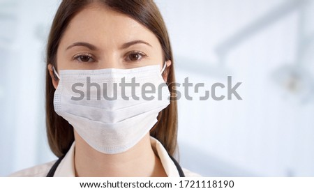 Portrait of confident professional female doctor in mask standing in hospital room. Woman physician at work. Health care concept #1721118190