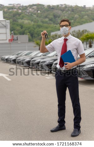 Sales Manager of a car show in a disposable protective mask on his face The concept of mandatory wearing of masks in the fight against COVID-19 #1721168374