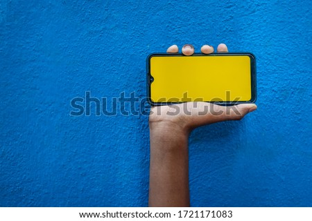 Boy hand showing mobile smartphone screen in orange Color with Isolated on blue background. Mobile phone screen on blue background with space for text.