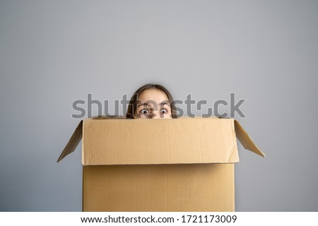 Think outside the box concept. Funny girl with scared face looking out of box at grey background. Getting out of comfort zone.