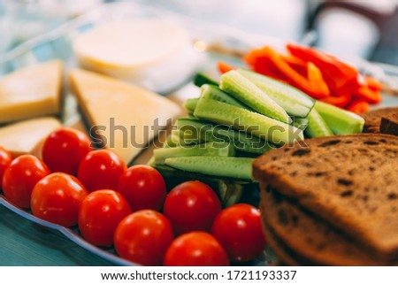 Close-up buffet of cherry tomatoes, cucumbers, cheese and slices of black bread on the table. Soft focused picture. Snack before dinner. A healthy and balanced diet. Light breakfast. Good morning