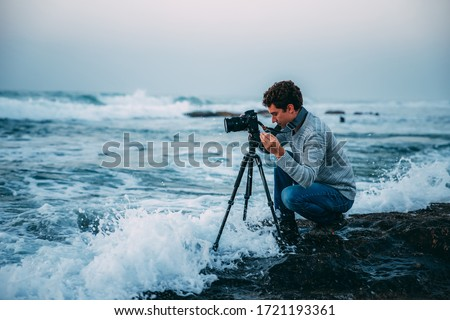 Young handsome photographer with curly hair, a gray sweater and jeans with a tripod and a camera on the beach, drenched in waves. Photography in Israel. Copy space. Shtorm on Mediterranean Sea