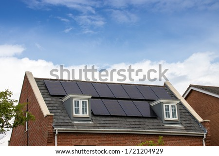 Photo of a modern British house in the UK with electrical solar panels on the roof on a bright sunny day with clouds in  the sky Royalty-Free Stock Photo #1721204929