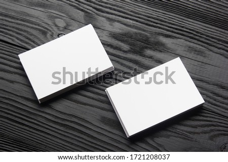 Business card blank on black wooden background. Corporate Stationery, Branding Mock-up. Creative designer desk. Flat lay. Copy space for text