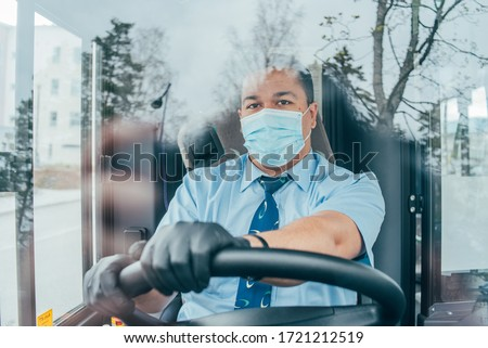 driver in mask looks at road while driving. young latin man bus driver in blue shirt has blue medical protection mask and black  gloves on hands.  bus driver wants to prevent  infection of covid 19. #1721212519
