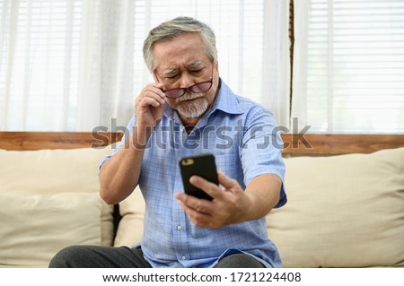 Senior people lifestyle health problem concept : Portrait photo of senior Asian man has a eye long sighted problem trying to read message from smartphone. Royalty-Free Stock Photo #1721224408