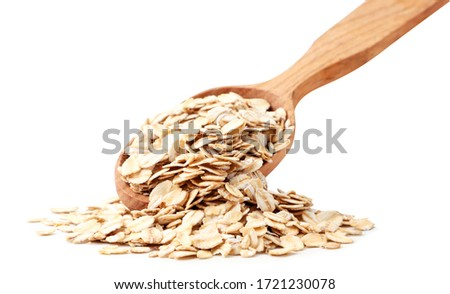 Oatmeal spills out of a wooden spoon on white background. Isolated #1721230078