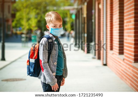 Schoolboy wearing face mask during epidemic. Back to school concept. Cute boy outside at school having good time. Safety mask to coronavirus prevention. Kid with backpack going to school. Education. #1721235490