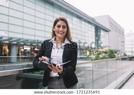 Delighted brunette female employee in white shirt and black jacket with grey pants leaning on glass fence holding notebook on blurred background of business center #1721235691