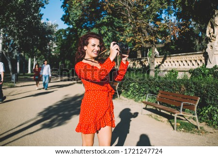 Beautiful caucasian female tourist in trendy red dress focusing via camera taking picture of urban setting during tour, smiling 20s woman photographer enjoying making photos on sunny day in town