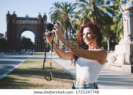 Cheerful brunette female tourist taking photo of beautiful city architecture on destination having trip on vacations, positive woman traveler exploring town checking focul on camera taking picture