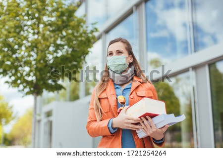 Student wearing mask during covid-19 cannot enter closed university building Royalty-Free Stock Photo #1721254264