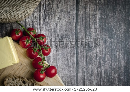 Sliced bread, butter, tomatoes and salt on a wooden board. Color food photography.